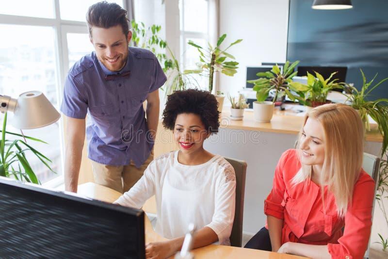 Ευτυχής δημιουργική ομάδα με τον υπολογιστή στην αρχή στοκ εικόνες