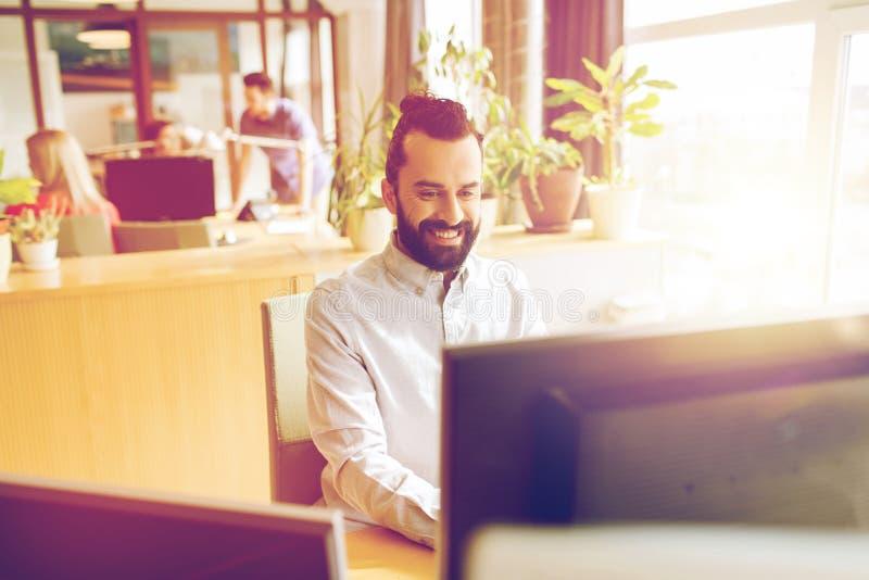 Ευτυχής δημιουργικός εργαζόμενος γραφείων αρσενικών με τον υπολογιστή στοκ εικόνες με δικαίωμα ελεύθερης χρήσης