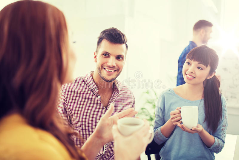Ευτυχής δημιουργικός καφές κατανάλωσης ομάδων στο γραφείο στοκ φωτογραφία με δικαίωμα ελεύθερης χρήσης