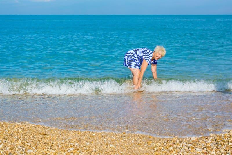 Ευτυχής ηλικιωμένη γυναίκα που απολαμβάνει στην παραλία στοκ εικόνες με δικαίωμα ελεύθερης χρήσης
