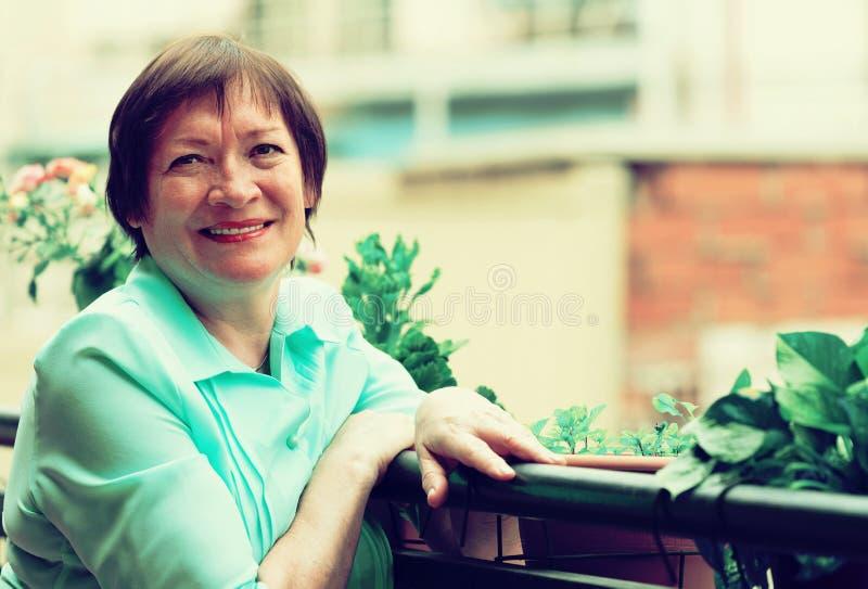 Ευτυχής ηλικιωμένη γυναίκα που απολαμβάνει το συμπαθητικό καιρό στοκ φωτογραφίες