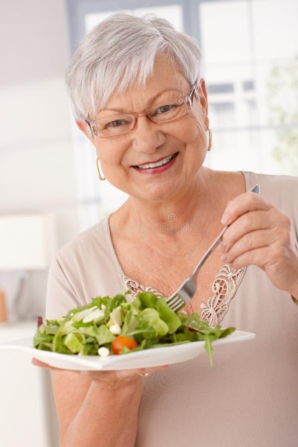 Ευτυχής ηλικιωμένη γυναίκα που τρώει την πράσινη σαλάτα στοκ εικόνες