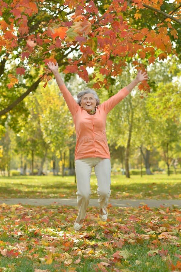 Ευτυχής ηλικιωμένη γυναίκα στο πάρκο φθινοπώρου στοκ φωτογραφίες με δικαίωμα ελεύθερης χρήσης