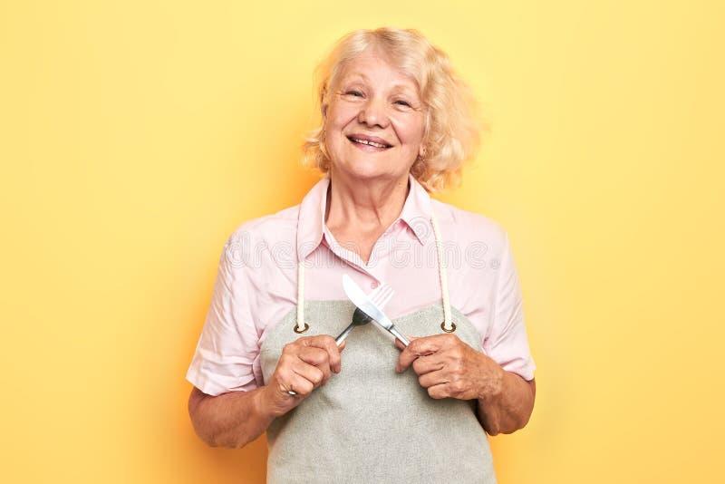 Ευτυχής θετική γυναίκα στην γκρίζα ποδιά με το διασχισμένα κουτάλι και το δίκρανο στοκ εικόνα