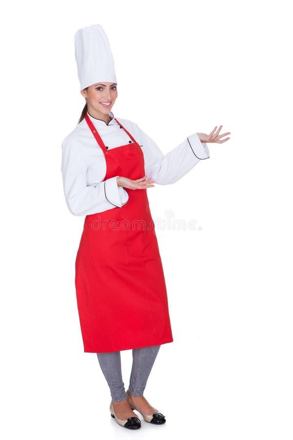 Ευτυχής θηλυκός αρχιμάγειρας Gesturing στοκ φωτογραφία