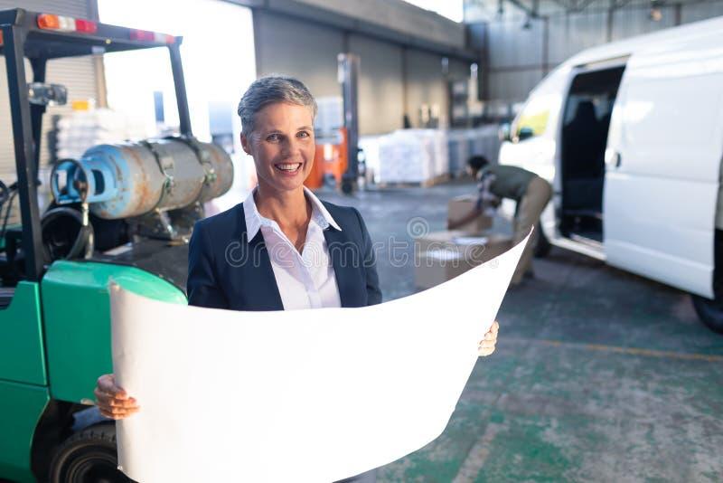 Ευτυχής θηλυκός διευθυντής που εξετάζει το σχεδιάγραμμα στην αποθήκη εμπορευμάτων στοκ εικόνα με δικαίωμα ελεύθερης χρήσης