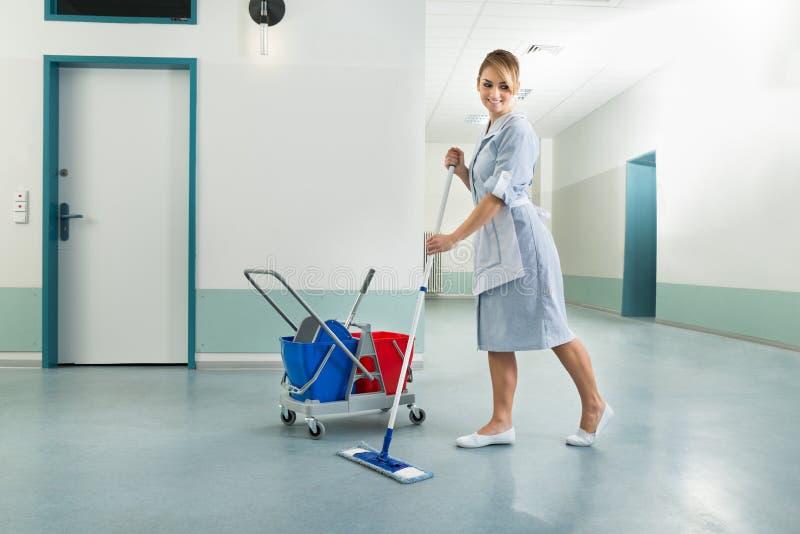 Ευτυχής θηλυκή janitor σφουγγαρίστρα εκμετάλλευσης στοκ φωτογραφία