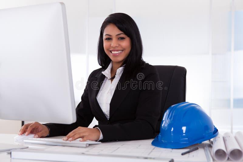 Ευτυχής θηλυκός αρχιτέκτονας που χρησιμοποιεί τον υπολογιστή στοκ φωτογραφίες με δικαίωμα ελεύθερης χρήσης