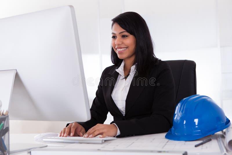 Ευτυχής θηλυκός αρχιτέκτονας που χρησιμοποιεί τον υπολογιστή στοκ εικόνες με δικαίωμα ελεύθερης χρήσης