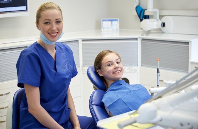 Ευτυχής θηλυκός οδοντίατρος με το υπομονετικό κορίτσι στην κλινική στοκ εικόνες