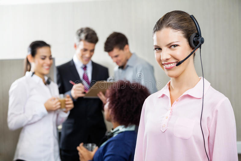 Ευτυχής θηλυκός πράκτορας υπηρεσιών που στέκεται στο τηλεφωνικό κέντρο στοκ φωτογραφίες