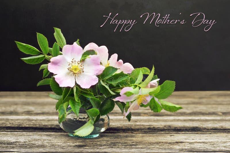 Ευτυχής κάρτα ημέρας μητέρων Ακόμα ζωή με τα άγρια τριαντάφυλλα στο υπόβαθρο grunge στοκ εικόνες