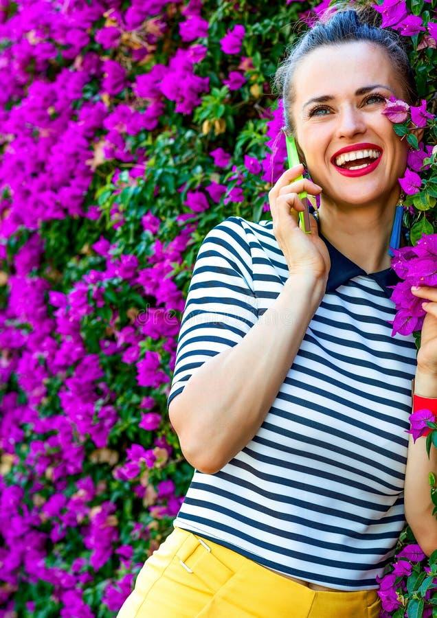 Ευτυχής καθιερώνουσα τη μόδα γυναίκα κοντά στο κρεβάτι λουλουδιών που μιλά στο τηλέφωνο κυττάρων στοκ φωτογραφία