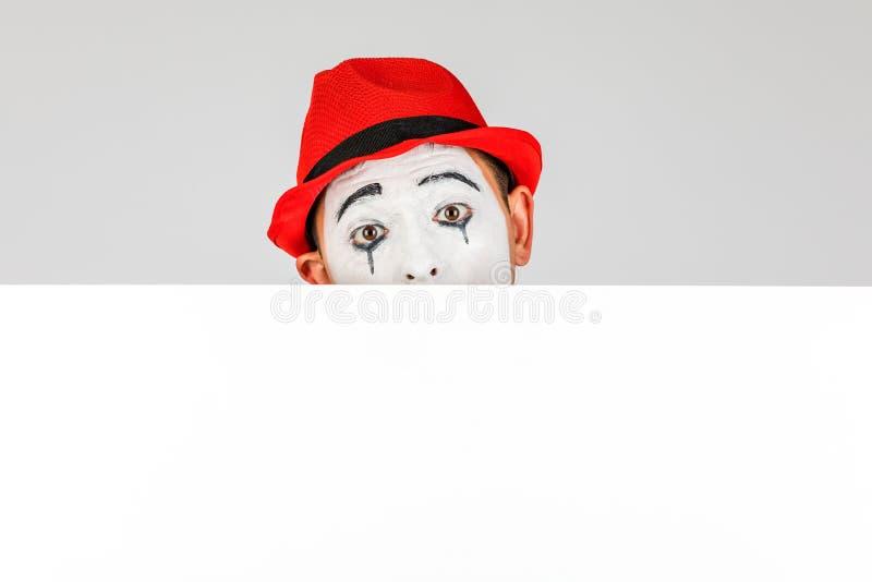ευτυχής καλλιτέχνης MIME που κρατά έναν κενό λευκό πίνακα, σε ένα άσπρο backgr στοκ εικόνες με δικαίωμα ελεύθερης χρήσης