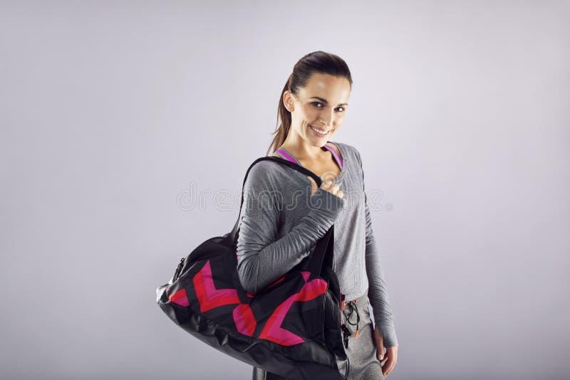 Ευτυχής κατάλληλη νέα γυναίκα με την τσάντα γυμναστικής στοκ εικόνες με δικαίωμα ελεύθερης χρήσης