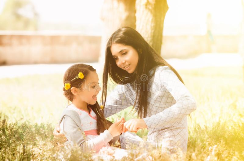 ευτυχής κατοχή οικογε& το κοριτσάκι με τη σγουρή τρίχα και τη μητέρα του χαμογελά το ένα το άλλο υπαίθριο πλάνο νησιών πτώσης ομι στοκ εικόνες