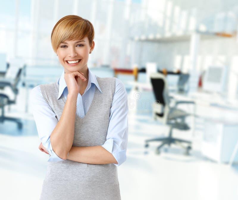 Ευτυχής καυκάσια γυναίκα στο γραφείο στοκ φωτογραφία