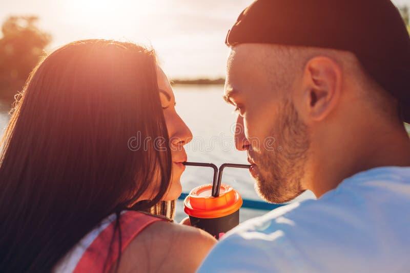 Ευτυχής καφές κατανάλωσης ζευγών ερωτευμένος μαζί με ένα άχυρο από τον ποταμό στο ηλιοβασίλεμα στοκ φωτογραφίες