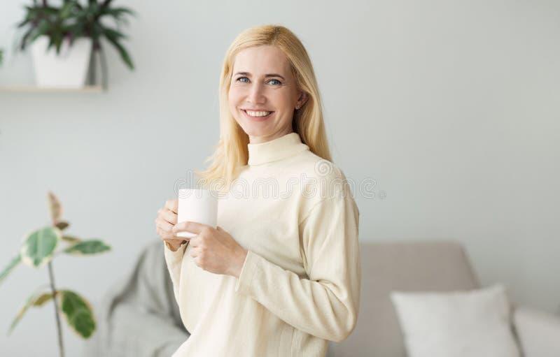 Ευτυχής καφές πρωινού κατανάλωσης γυναικών, που στηρίζεται στο σπίτι στοκ εικόνες