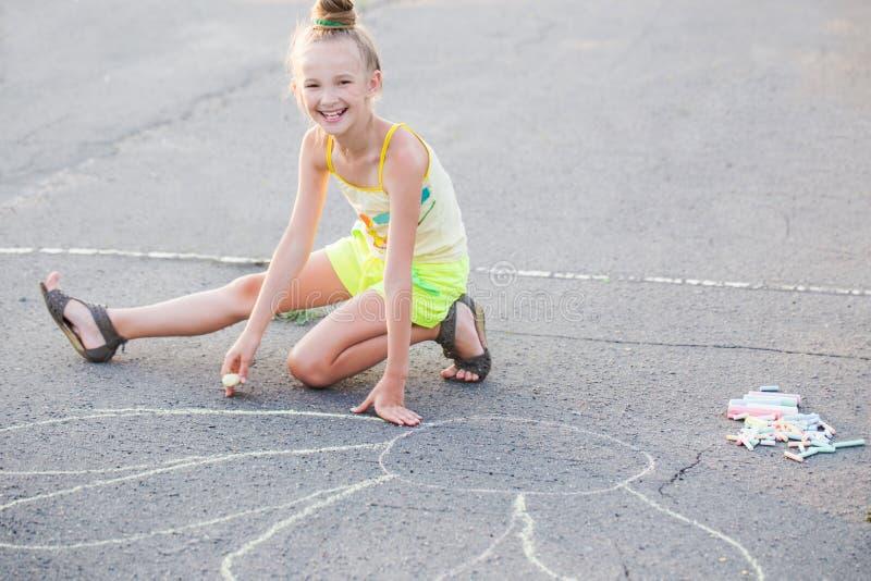 Ευτυχής κιμωλία σχεδίων κοριτσιών στην άσφαλτο στοκ φωτογραφίες