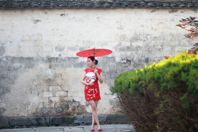 Ευτυχής κινεζική γυναίκα στον κόκκινο γύρο cheongsam στην αρχαία πόλη στοκ φωτογραφίες