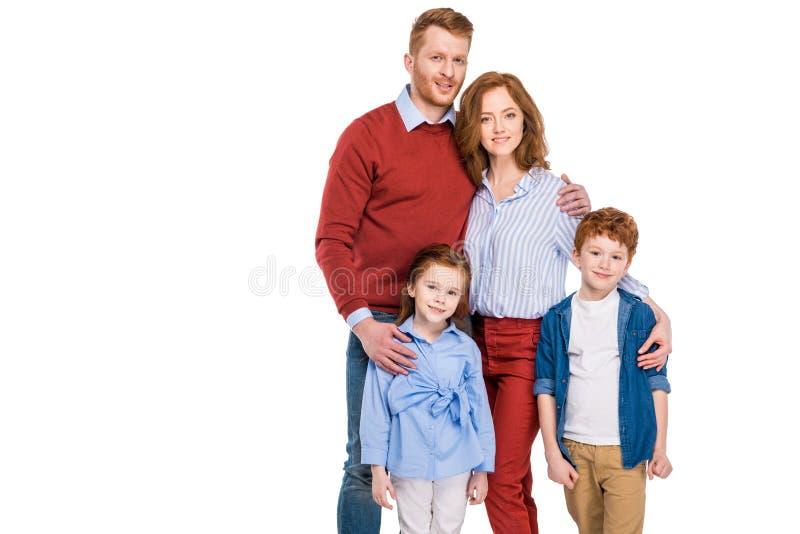 ευτυχής κοκκινομάλλης οικογένεια με δύο παιδιά που στέκονται μαζί και που χαμογελούν στη κάμερα στοκ εικόνες
