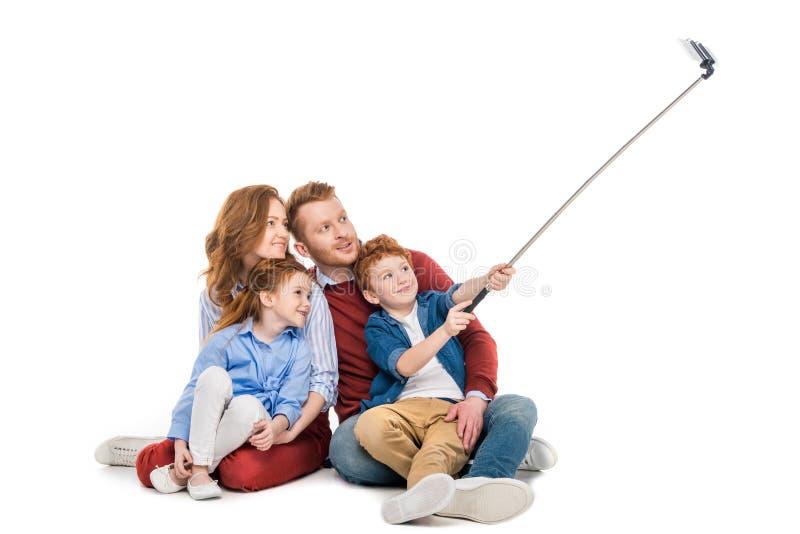 ευτυχής κοκκινομάλλης οικογενειακή συνεδρίαση μαζί και παίρνοντας selfie με το smartphone στοκ εικόνα με δικαίωμα ελεύθερης χρήσης