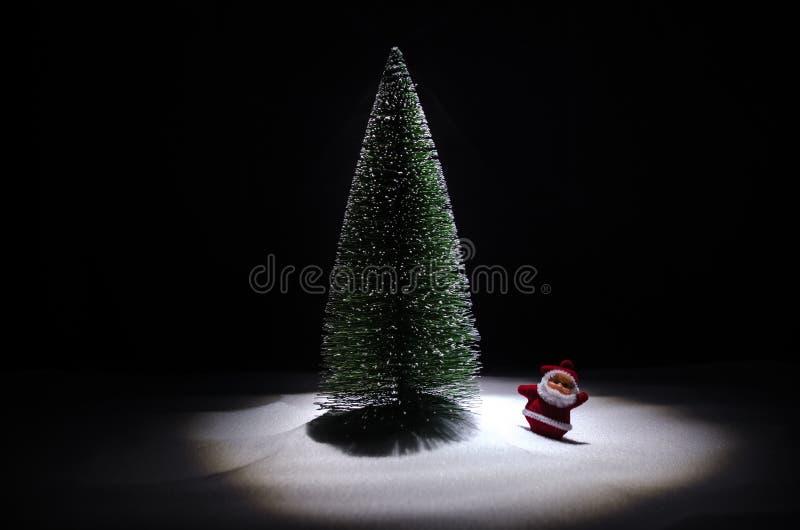 Ευτυχής κούκλα Άγιου Βασίλη στο χρόνο Χριστουγέννων με το δέντρο και το χιόνι ανασκόπηση bokeh ζωηρόχρωμη Άγιος Βασίλης και πρότυ στοκ εικόνα με δικαίωμα ελεύθερης χρήσης