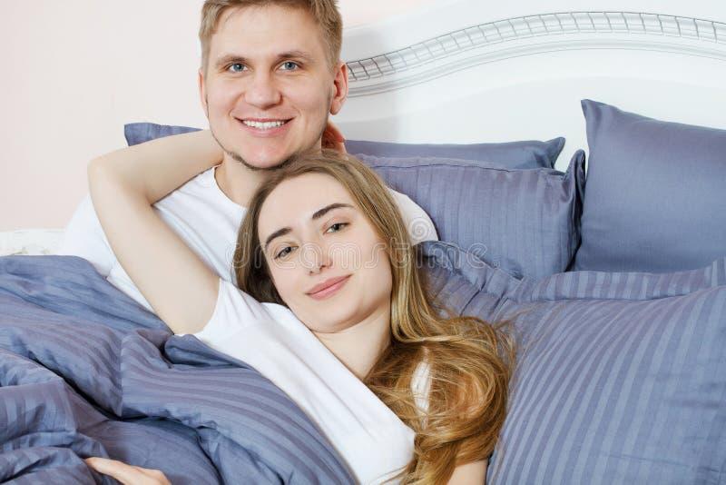 Ευτυχής κρεβατοκάμαρα κρεβατιών ζευγών πορτρέτου το πρωί, ευτυχής οικογένεια, υγιής έννοια ύπνου στοκ εικόνα