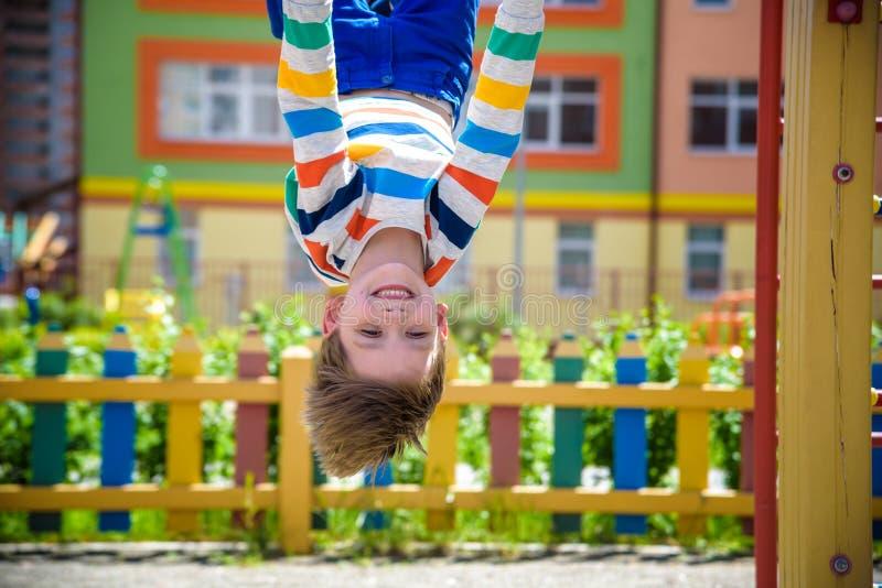 Ευτυχής κρεμώντας άνω πλευρά αγοριών παιδιών - κάτω στο φραγμό, παιδική χαρά στην πόλη, υπαίθριες δραστηριότητες στοκ φωτογραφίες με δικαίωμα ελεύθερης χρήσης