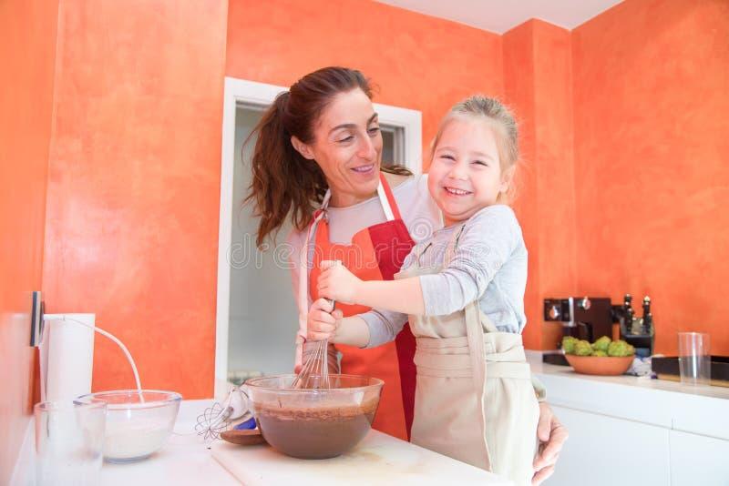 Ευτυχής κτυπώντας σοκολάτα παιδιών με τη μητέρα στοκ φωτογραφίες με δικαίωμα ελεύθερης χρήσης