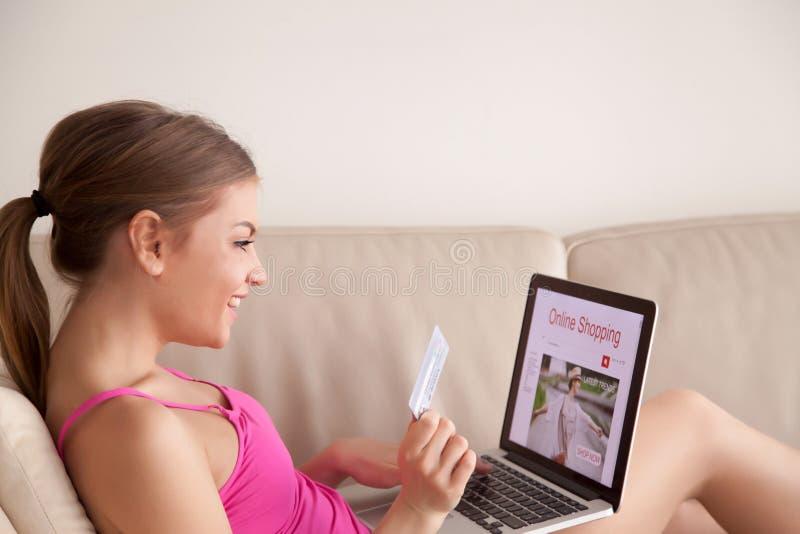 Ευτυχής κυρία που αγοράζει τα μοντέρνα ενδύματα on-line στοκ εικόνα με δικαίωμα ελεύθερης χρήσης
