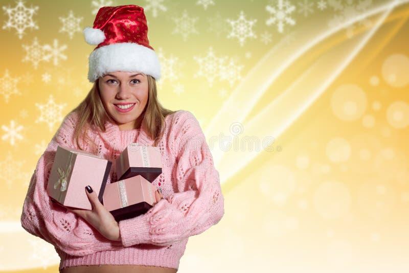 Ευτυχής κυρία που φορά τα δώρα εκμετάλλευσης καπέλων Santa επάνω στοκ φωτογραφία με δικαίωμα ελεύθερης χρήσης