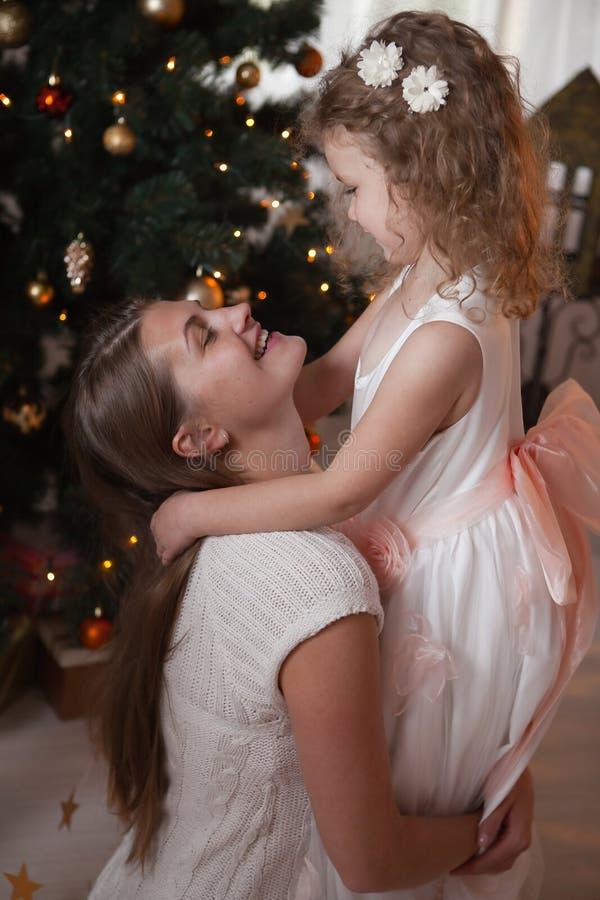 Ευτυχής κόρη αγκαλιάσματος μητέρων στο χριστουγεννιάτικο δέντρο στοκ εικόνες