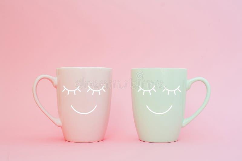 Ευτυχής λέξη Παρασκευής Δύο φλιτζάνια του καφέ στέκονται μαζί να είναι μορφή καρδιών στο ρόδινο υπόβαθρο με το πρόσωπο χαμόγελου  στοκ φωτογραφία με δικαίωμα ελεύθερης χρήσης