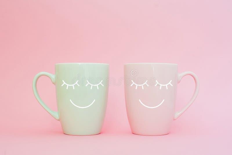 Ευτυχής λέξη Παρασκευής Δύο φλιτζάνια του καφέ στέκονται μαζί να είναι μορφή καρδιών στο ρόδινο υπόβαθρο με το πρόσωπο χαμόγελου  στοκ εικόνες με δικαίωμα ελεύθερης χρήσης