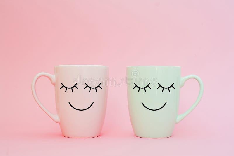 Ευτυχής λέξη Παρασκευής Δύο φλιτζάνια του καφέ στέκονται μαζί να είναι μορφή καρδιών στο ρόδινο υπόβαθρο με το πρόσωπο χαμόγελου  στοκ φωτογραφίες