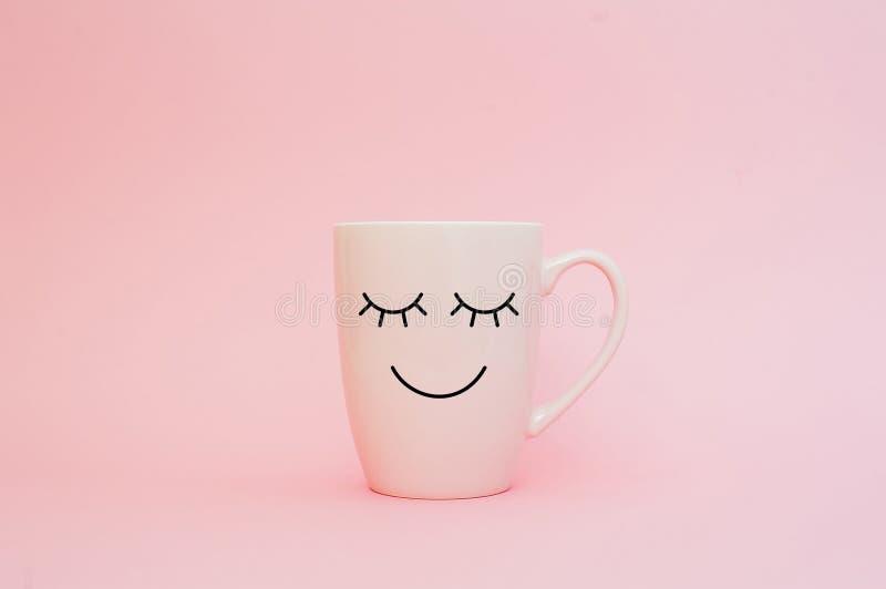 Ευτυχής λέξη Παρασκευής Φλιτζάνι του καφέ στο ρόδινο υπόβαθρο με το πρόσωπο χαμόγελου στην κούπα Έννοια για την αγάπη και τη σχέσ στοκ φωτογραφίες