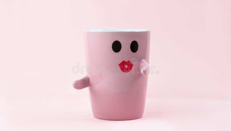 Ευτυχής λέξη Παρασκευής Φλιτζάνι του καφέ στο ρόδινο υπόβαθρο με το πρόσωπο χαμόγελου στην κούπα Έννοια για την αγάπη και τη σχέσ στοκ εικόνες