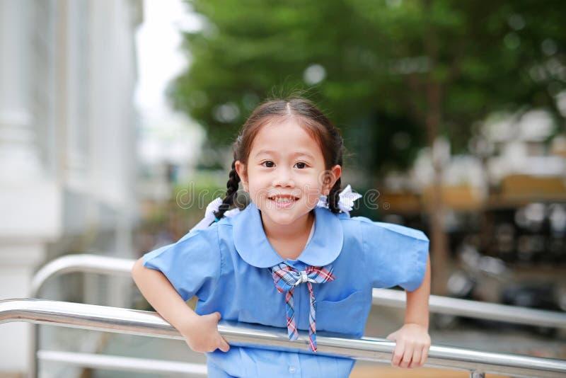 Ευτυχής λίγο ασιατικό κορίτσι στην εύθυμη ένωση σχολικών στολών στο κιγκλίδωμα μετάλλων στοκ φωτογραφία με δικαίωμα ελεύθερης χρήσης