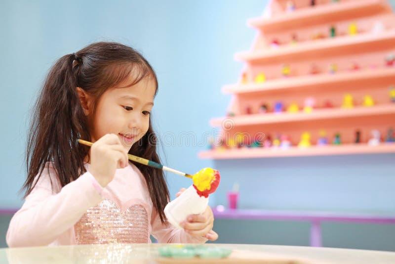Ευτυχής λίγο κορίτσι παιδιών που έχει τη διασκέδαση για να χρωματίσει στην κούκλα στόκων εσωτερική στοκ φωτογραφία με δικαίωμα ελεύθερης χρήσης