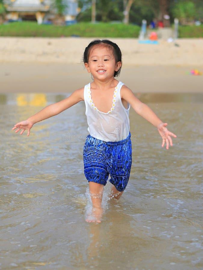 Ευτυχής λίγο κορίτσι παιδιών που τρέχει στην παραλία στους θερινούς χρόνους στοκ εικόνες
