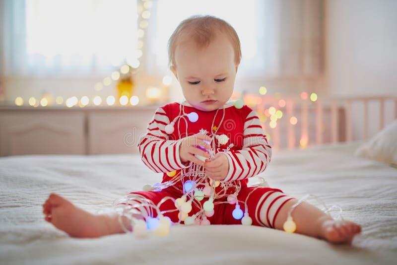 Ευτυχής λίγο κοριτσάκι που φορά τις πυτζάμες που παίζουν με τις νέες διακοσμήσεις δέντρων έτους στοκ φωτογραφία με δικαίωμα ελεύθερης χρήσης