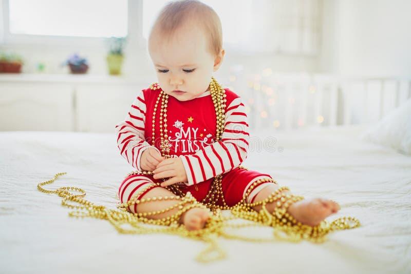 Ευτυχής λίγο κοριτσάκι που φορά τις πυτζάμες που παίζουν με τις νέες διακοσμήσεις δέντρων έτους στοκ εικόνες