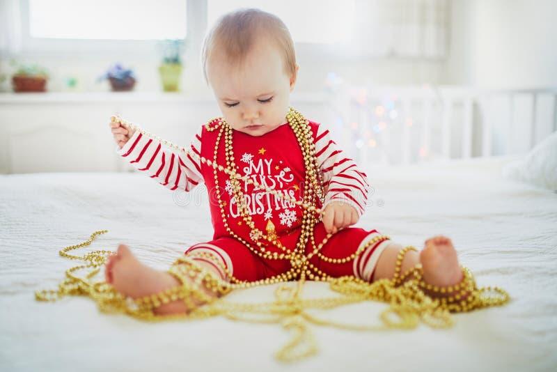 Ευτυχής λίγο κοριτσάκι που φορά τις πυτζάμες που παίζουν με τις νέες διακοσμήσεις δέντρων έτους στοκ εικόνα