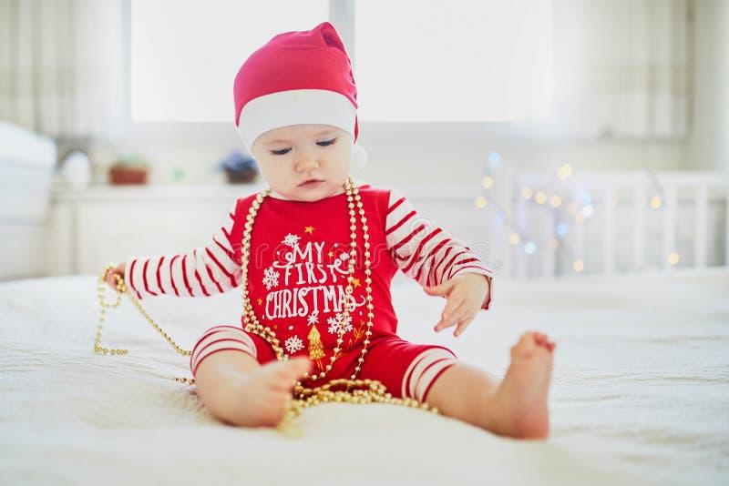 Ευτυχής λίγο κοριτσάκι που φορά τις πυτζάμες που παίζουν με τις νέες διακοσμήσεις δέντρων έτους στοκ φωτογραφίες