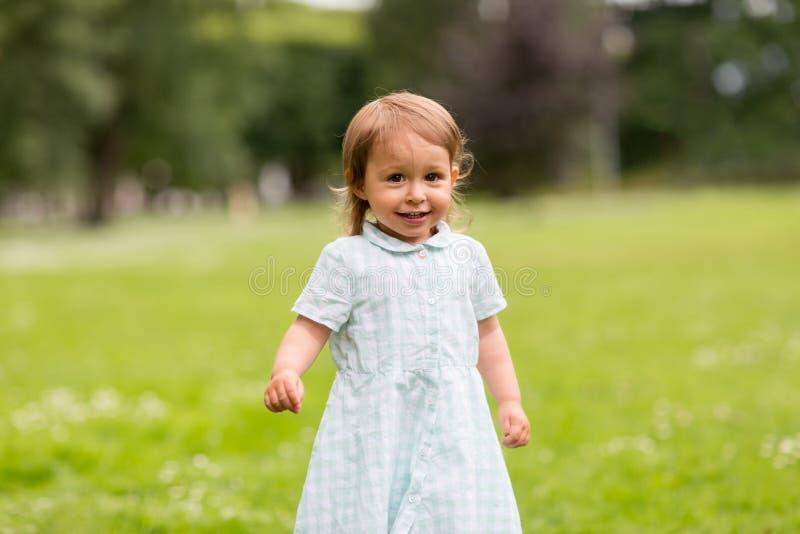 Ευτυχής λίγο κοριτσάκι στο πάρκο το καλοκαίρι στοκ εικόνα