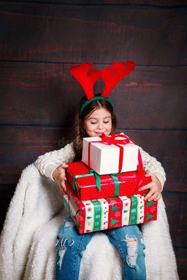 Ευτυχής λίγο χαμογελώντας κορίτσι με τα κιβώτια δώρων Χριστουγέννων Έννοια Χριστουγέννων Χαμογελώντας αστείο παιδί στα κέρατα ελα στοκ εικόνα