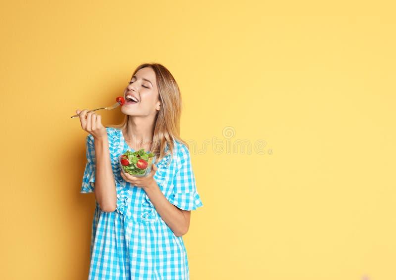 Ευτυχής λεπτή γυναίκα με τη σαλάτα στο υπόβαθρο χρώματος στοκ φωτογραφίες