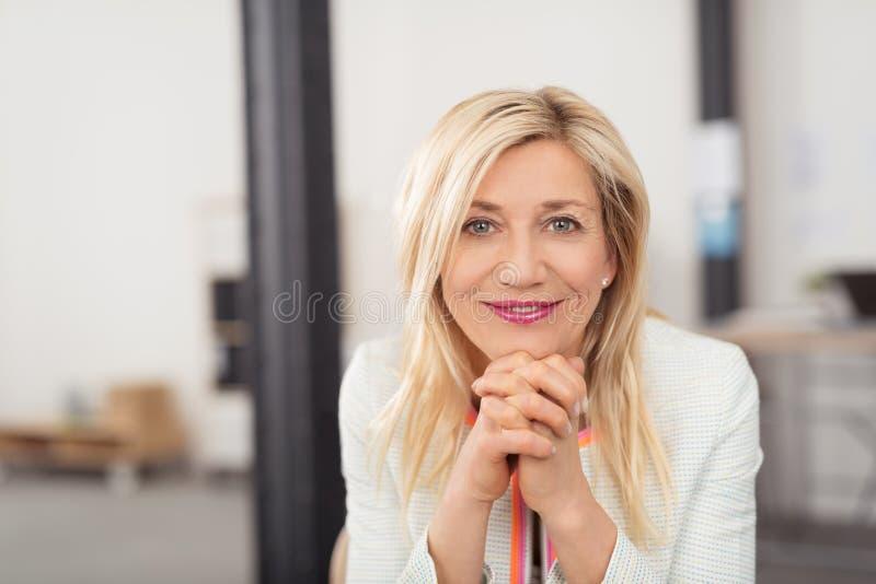 Ευτυχής μέσης ηλικίας γυναίκα με ένα φιλικό χαμόγελο στοκ εικόνα με δικαίωμα ελεύθερης χρήσης